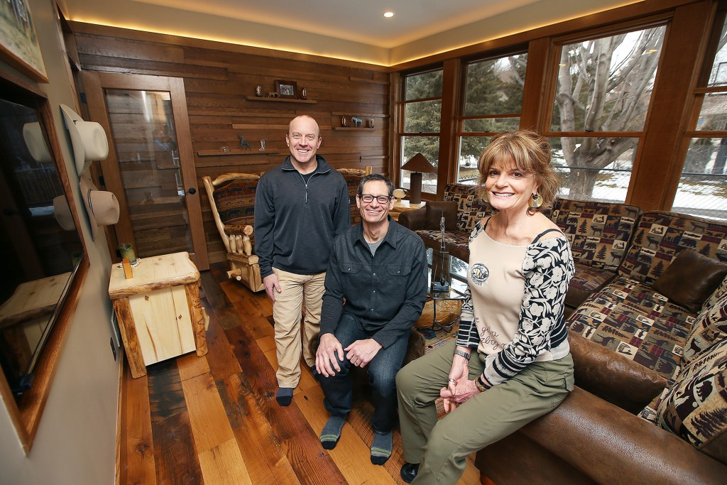 Carl Unger, left, and Nate Tollefson of Craft Design Build with homeowner Caryn Schall in the new year-round room they created in a former three-season porch.