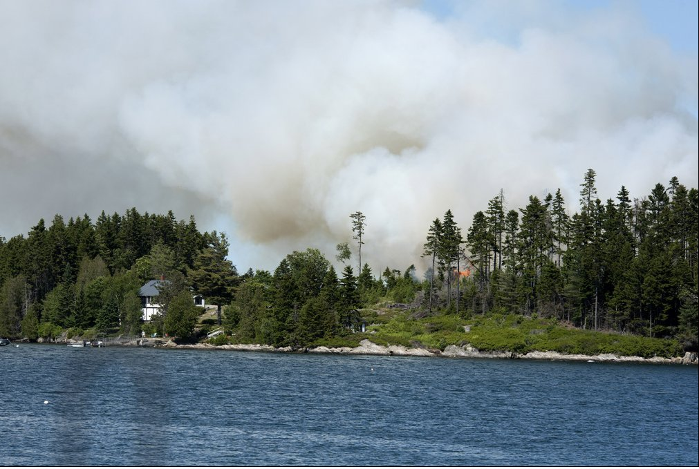 Smoke rises over Sheep Island inn Casco Bay, where about 4 acres burned Friday.