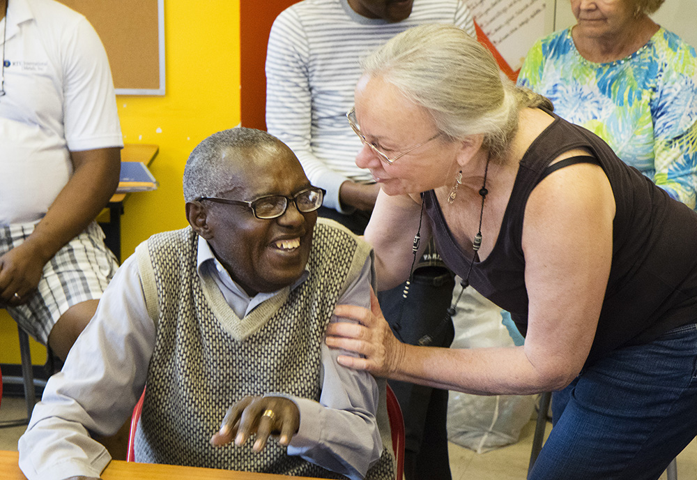 "Gaspard Kajangwe, who immigrated from the Democratic Republic of the Congo four years ago, greets Lewiston-born Cecile Thornton at the Hillview Adult French Club. Thornton joined the club to try and improve her French speaking abilities, but now says club members have ""become a family."""