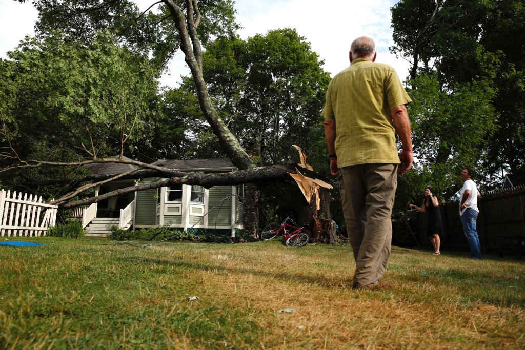 Stonemason Barry Shaw takes in the scene of destruction after a swift-moving squall knocked down several trees on Peaks Island, including one that narrowly missed a house at on Brackett Street. A chimney that Shaw built at the home withstood some of the impact without any noticeable damage.
