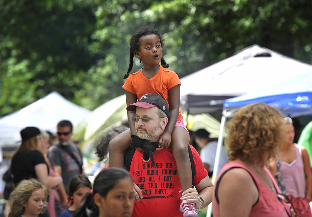 Edel Rimkunas, 4, of Gorham, who is originally from Ethiopia, enjoys the sights and sounds of the Festival of Nations Saturday at Deering Oaks Park from the shoulders of her father Tony Rimkunas. Edel was adopted by Tony. Shawn Patrick Ouellette/Staff Photographer