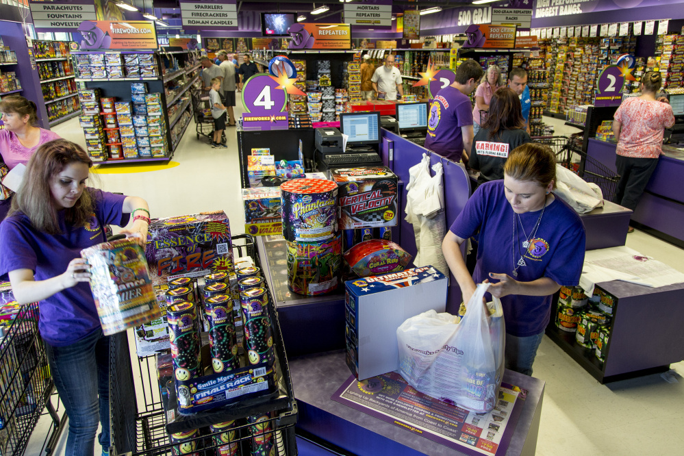 Caylie Westerhold and Taylor Sassano of Phantom Fireworks bag up an order worth hundreds of dollars at the Scarborough store Friday in preparation for Independence Day on Monday. Numerous signs are posted throughout the store warning customers of the dangers of using fireworks, and how to properly light them and extinguish them.
