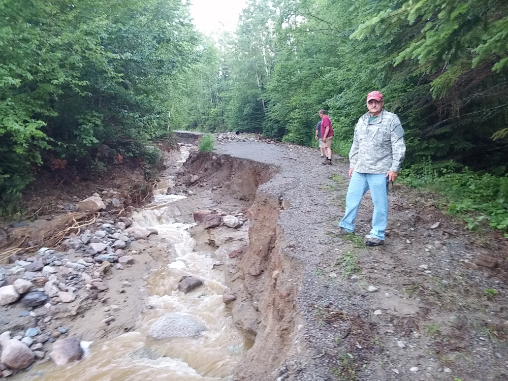 Rep. Larry Dunphy, of Embden, stands by a washed-out road Wednesday in northwestern Somerset County. Dunphy said he is trying to help secure financial help for residents of the area to fix the damage, which is estimated to cost nearly $1 million.