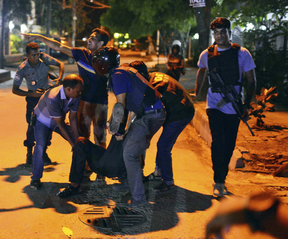 A wounded person is tended to after gunmen attacked a restaurant popular with foreigners in a diplomatic zone of the Bangladeshi capital of Dhaka on Friday.