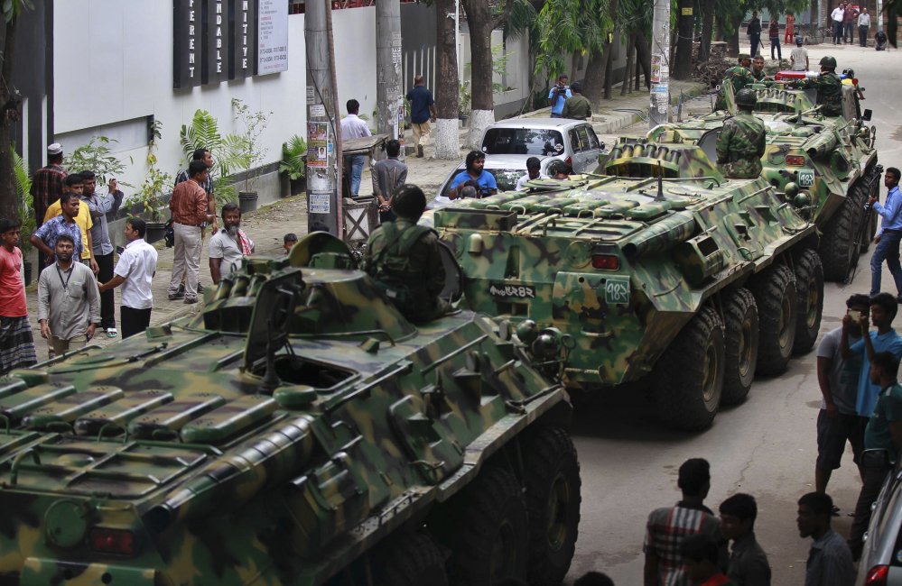 Armored vehicles pass by after an operation against militants who took hostages at a restaurant popular with foreigners in Dhaka, Bangladesh, Friday night, leaving at least 28 dead after a dramatic 10-hour siege.