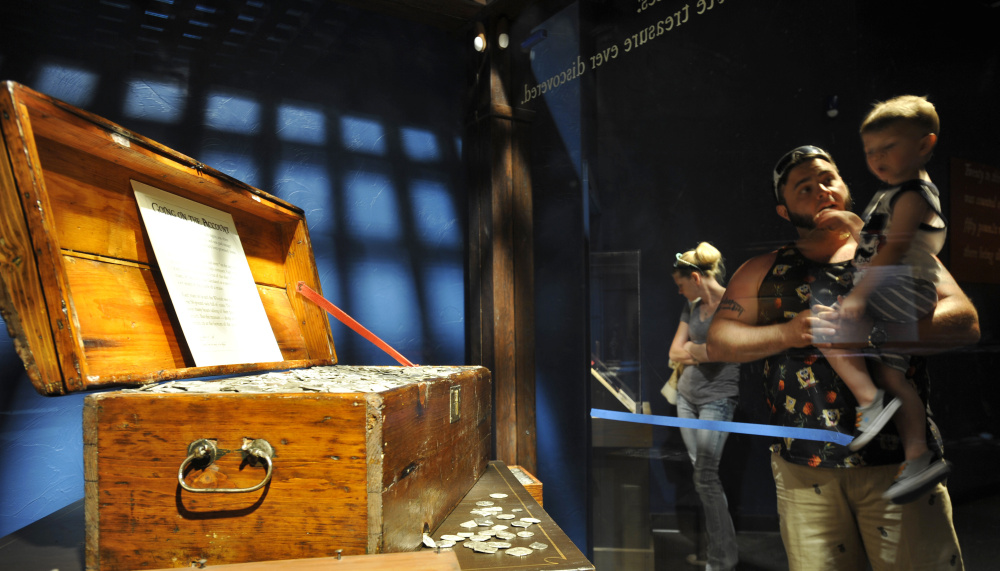 James Mante holds his 2-year-old son, Lucas, as they gaze at a large chest full of silver coins at the newly opened Whydah Pirate Museum.