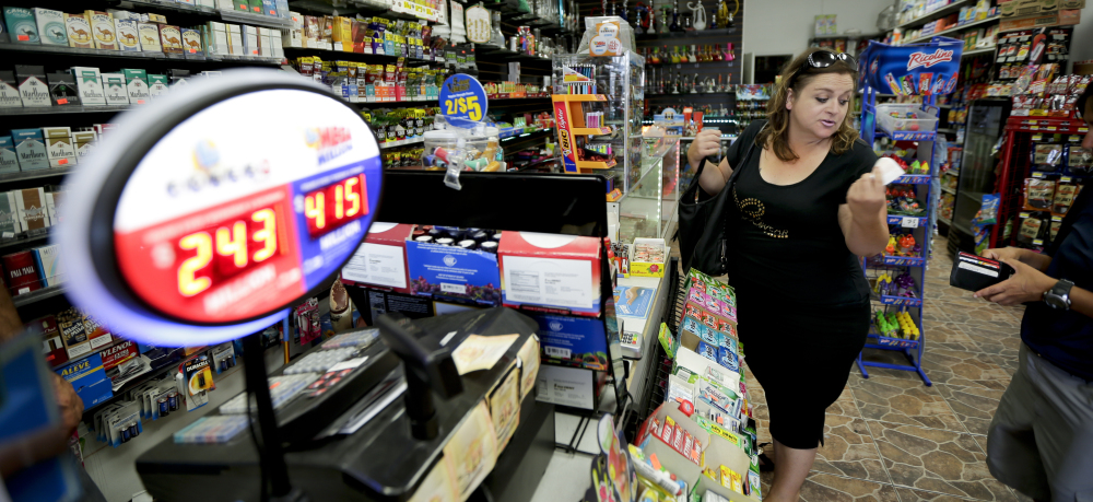 Diana Moore buys a Mega Millions lottery ticket Friday in San Diego. The odds for picking the correct numbers on five white balls and one yellow ball in the Mega Millions are one in 259 million. Tuesday's jackpot will be the largest since a $430 million Powerball win in May.