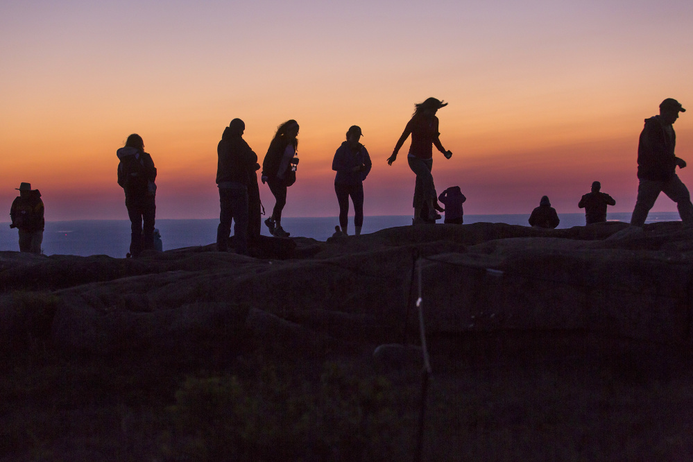 Visitors amble along the summit of Cadillac Mountain at dawn Monday. Acadia has been attracting ever-increasing crowds that some fear will threaten to fundamentally alter the experience of the park's natural beauty.
