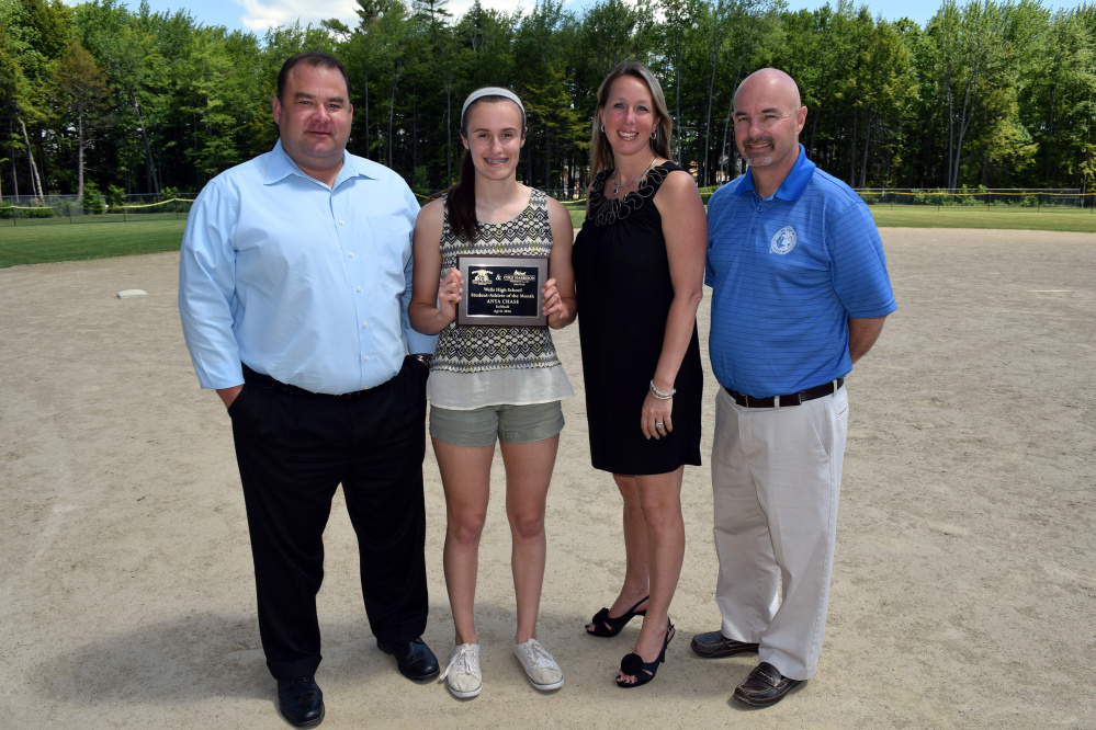 Wells High School student Anya Chase holds the Student Athlete of the Month plaque recognizing her contributions to the student body and community and excellence in academics and athletics. With Chase are award sponsors John C. Kreie of Cole Harrison Insurance Agency, left; Pam Moody-Maxon of Moody Maxon Real Estate and WHS Director of Student Activities Jack Molloy.