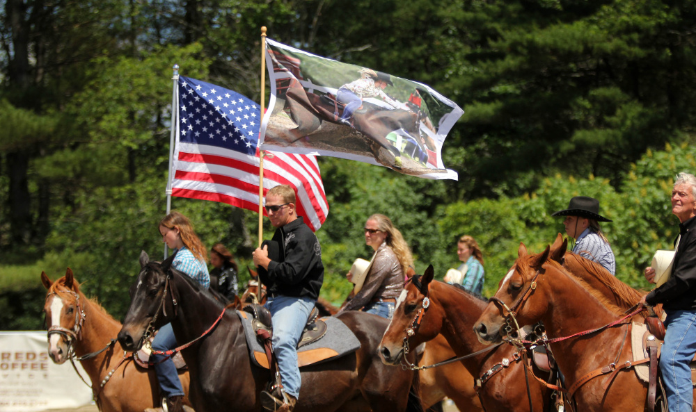 Hardy Cummings holds a flag with a photo of his late daughter before the start of the Halee Cummings Memorial Barrel Race in Sidney on Sunday.