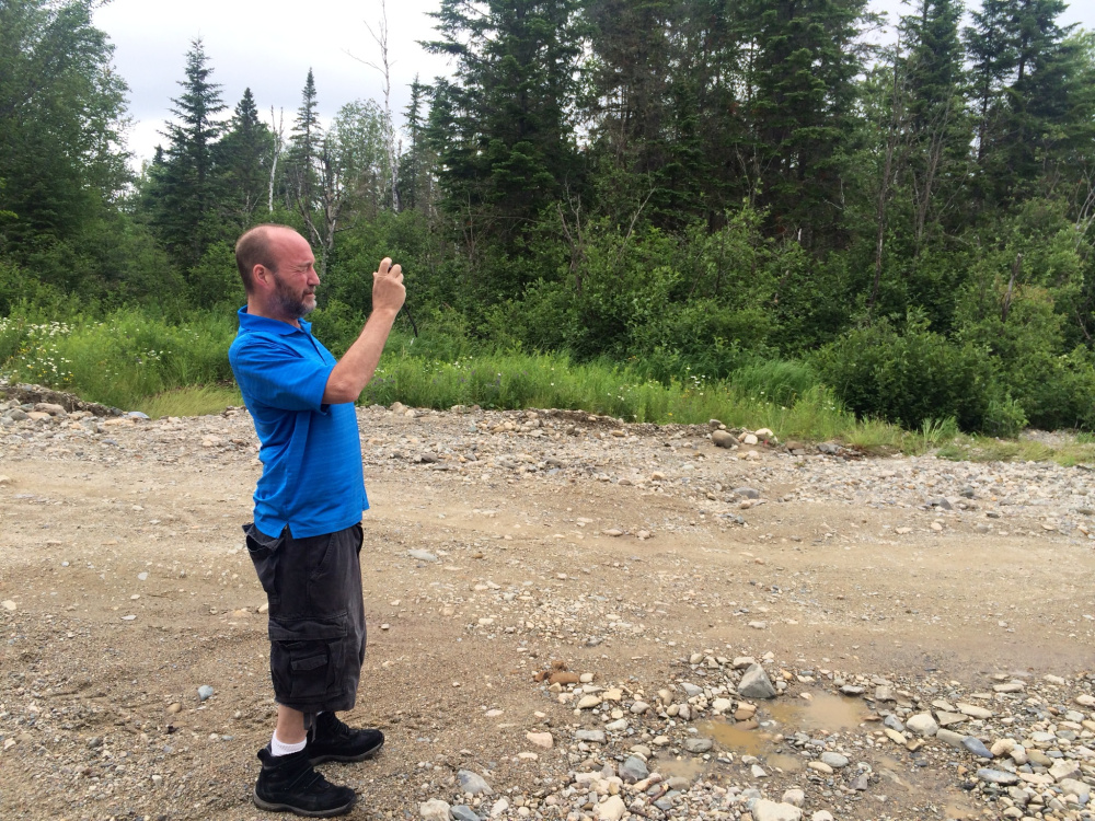James York takes photos of the damage on Spencer Road in Upper Enchanted Township on Saturday.