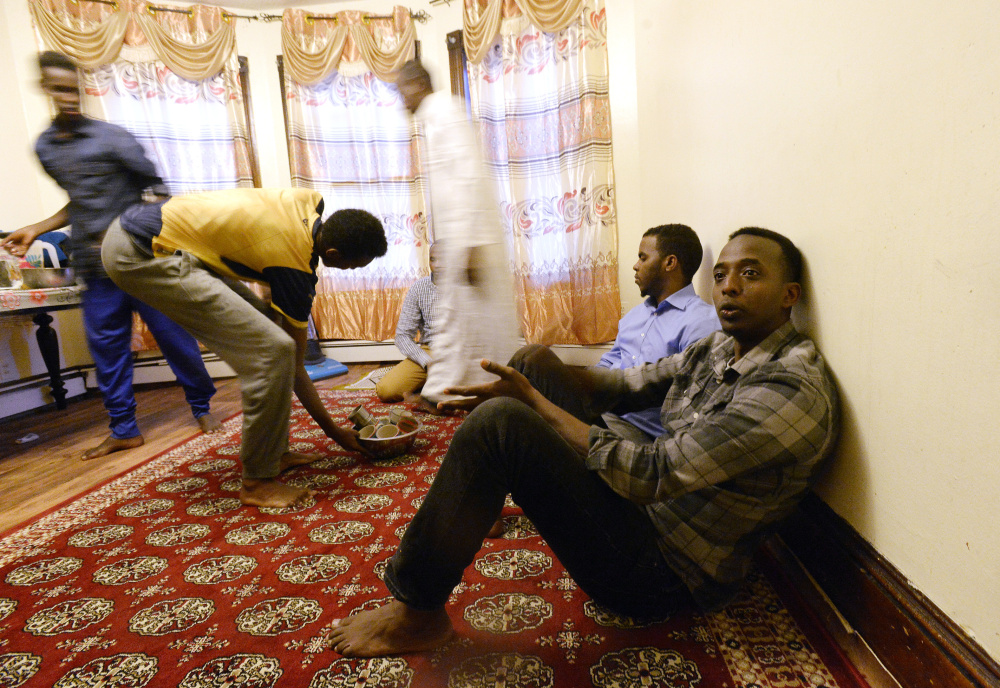 Abdi Nor Iftin sits with fellow Maine Somalis as food is brought out for an iftar, the traditional sunset meal Muslims eat to break the fast of Ramadan, last Tuesday evening in Lewiston.