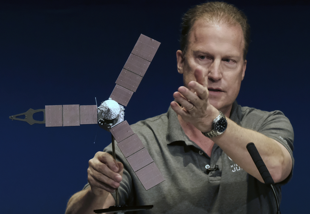 Rick Nybakken, Juno project manager, holds a model of the Juno spacecraft at a briefing at the Jet Propulsion Laboratory in Pasadena, Calif., on Monday while talking about the solar panels and the orbit it will take around Jupiter. The solar-powered spacecraft was on its way toward Jupiter for the closest encounter with the biggest planet in our solar system.
