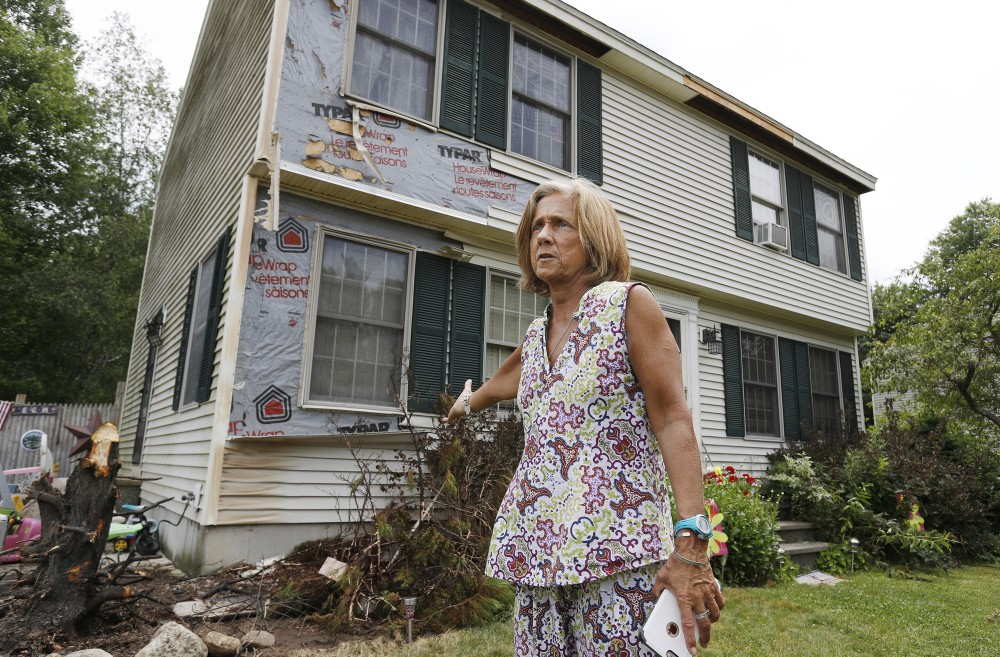 Julie Klippert stands Tuesday near the area of her house that was singed when a stray firework set a tree on fire. The stump of the tree, which had been removed, is at left.