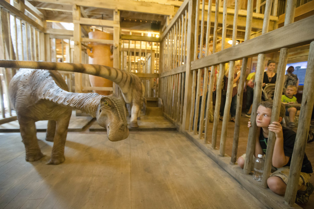 A visitor looks into a cage containing a model dinosaur inside the replica Noah's ark. The ministry behind the project expects 2 million visitors in the first year.