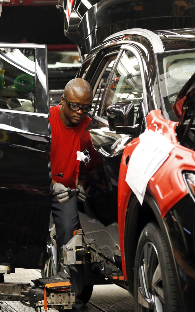 A technician works on a Nissan Altima at the plant in Canton, Miss.