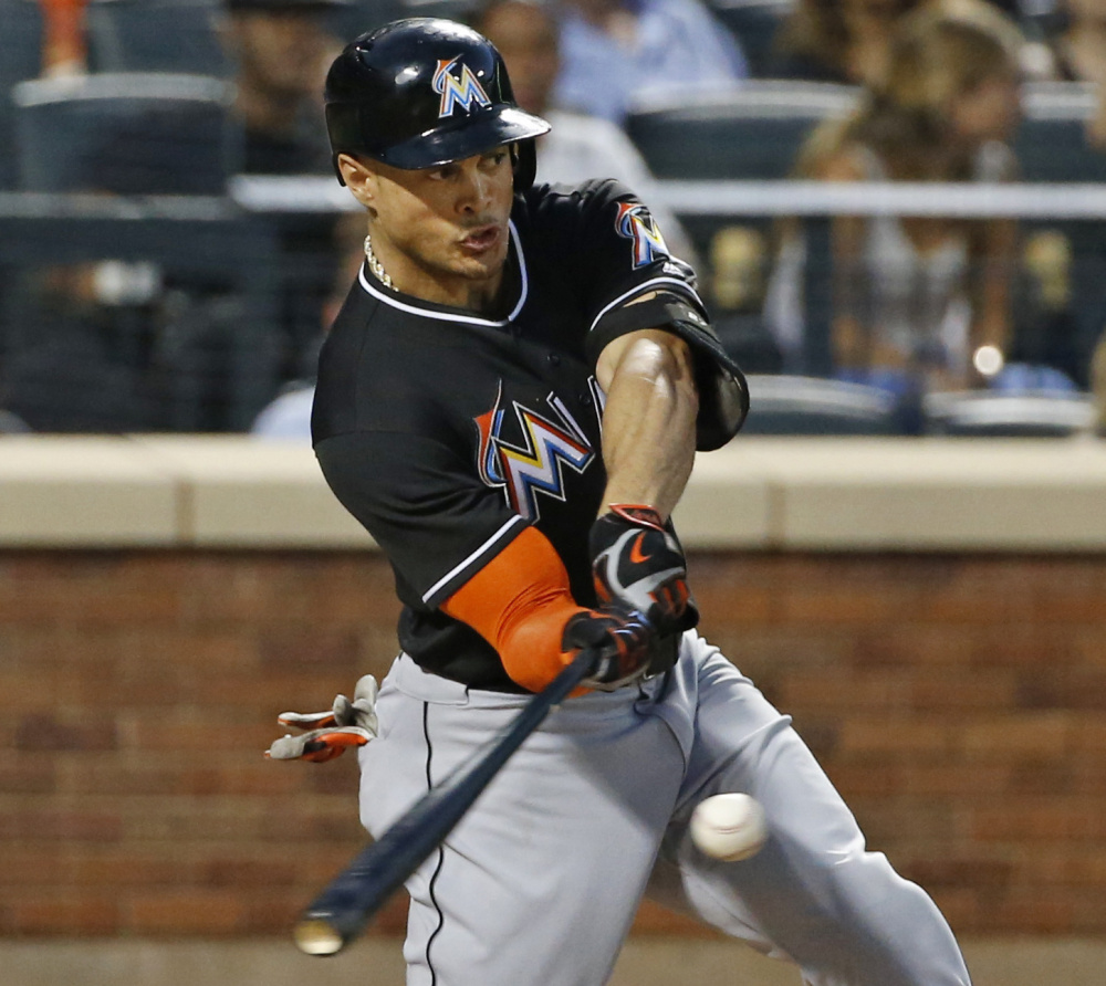 Giancarlo Stanton of the Miami Marlins hits a two-run homer Tuesday night in the seventh inning of the 5-2 victory against the New York Mets.