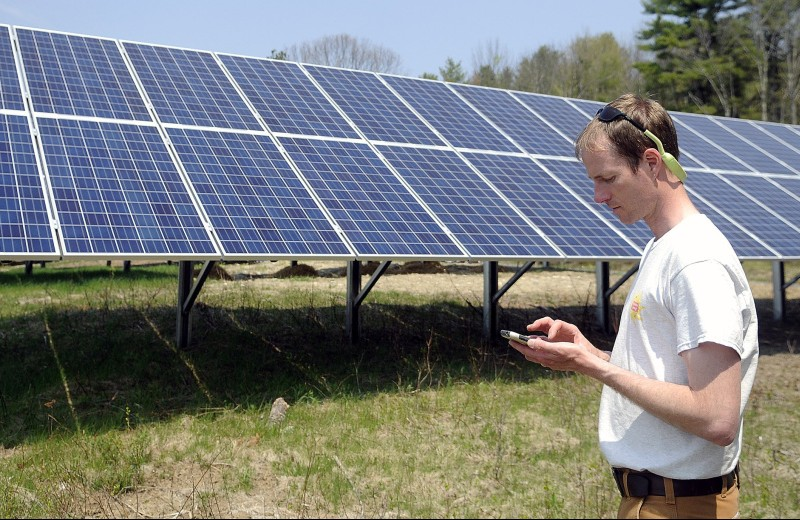 Hans Albee, an engineer at the ReVision Energy solar company in Portland, checks the Sky Ranch Solar Farm in the Kennebec County town of Wayne, which is owned by a group of community members. The Wayne project went online in May and can produce 49.6 kilowatts of power.