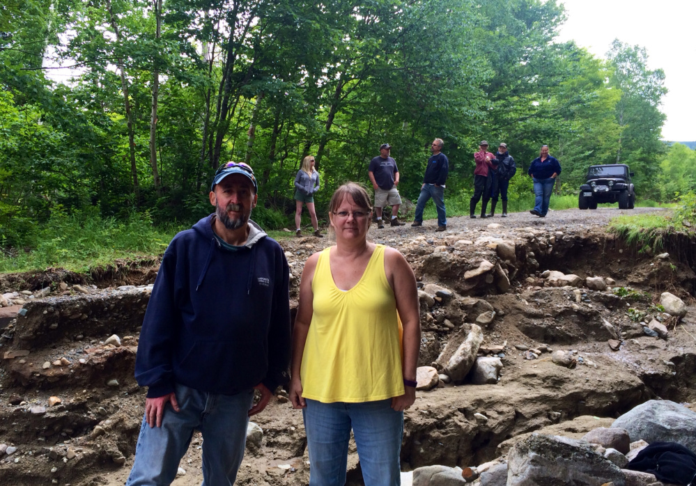 Norman and Lisa Lapointe, of Vassalboro, stand in the middle of No Road, where they own a camp, while surveying damage from last week's flash floods with other property owners Saturday. The Lapointes are able to access their property via a 45-minute detour over other roads and ATV trails and said they are not sure how the local road association will be able to pay for repairs.