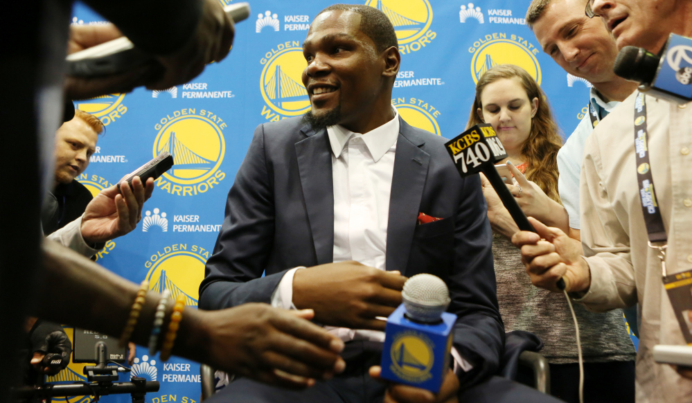 Kevin Durant speaks with reporters after his introductory news conference Thursday in Oakland, Calif., to announce his signing with the Golden State Warriors.