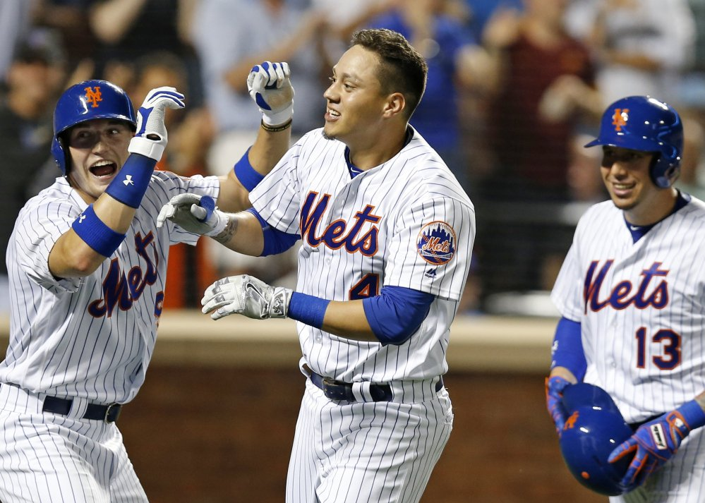 Brandon Nimmo, left, Wilmer Flores, center, and  Asdrubal Cabrera of the Mets celebrate after scoring on Flores' pinch-hit, three-run homer against the Nationals at New York on Thursday.