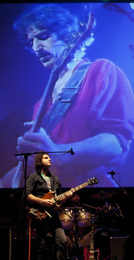 Dweezil Zappa performs in front of a projection of his late father, Frank, in Bristol, England, in 2011.
