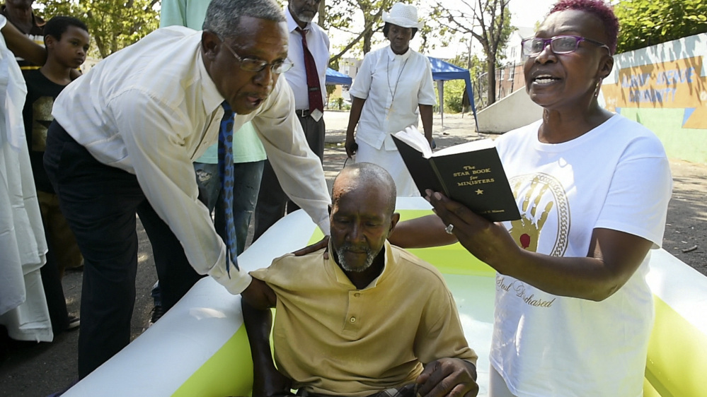 Pastor Gerald Miller, left, helps Pastor Lauri Andrews Malawitz support Willie Cannon as Malawitz prepares to baptize him in a small pool in Hartford, Conn., on June 26. Malawitz is the pastor of Effectual Fervent Prayer Outreach Ministries.