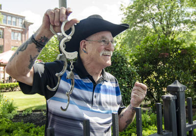 Retired escape artist Roger Lavoie holds handcuffs in Fitchburg, Mass. His feats of escape included freeing himself from an oil drum filled with angry tarantulas.