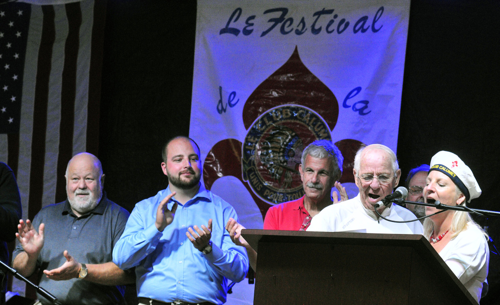 Larry Guimond and Rachel Boucher Ellis lead Le Club Calumet's anthem Friday during the opening night of Le Festival de La Bastille in Augusta. Earlier, Guimond had sung the Canadian anthem, Boucher Ellis the French anthem and Tina Charest the American.