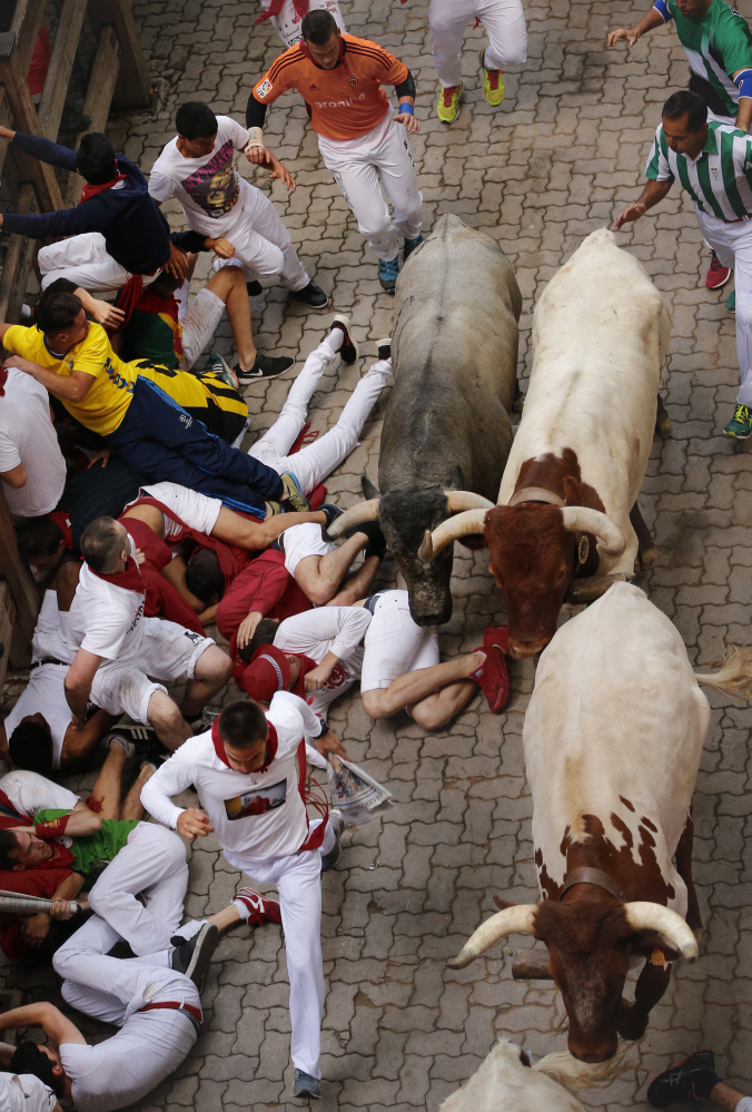 Revelers fall as they are chased by bulls running through the streets on Saturday in Pamplona, Spain, where more than 1,000 from around the world took part in the run.
