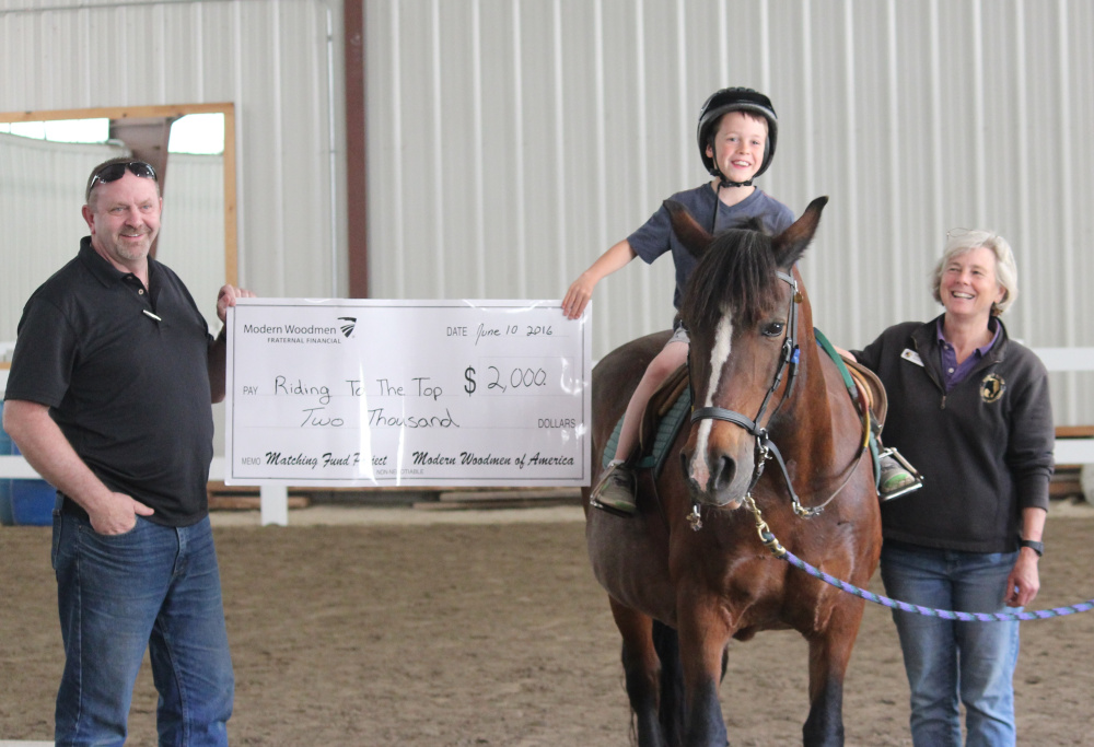Modern Woodmen of America's Tim Graham recently presented Riding to the Top Therapeutic Riding Center with a matching gift of $2,000 during the center's second annual Dances With Horses fundraising event.