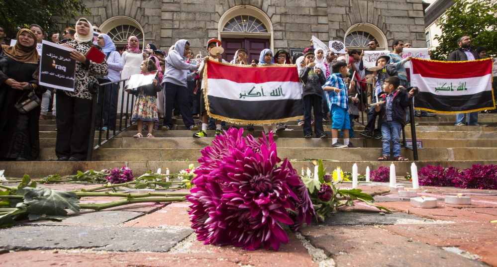 Flowers are placed at the steps of the First Parish Church in Portland on Sunday during a vigil to honor the victims of the July 3 terrorist attack in Baghdad. Ben McCanna/Staff Photographer