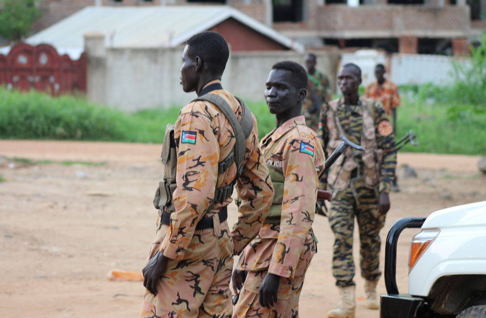 South Sudanese policemen and soldiers stand guard along a street following renewed fighting in South Sudan's capital of Juba on Sunday. Widespread casualties were reported in the city.