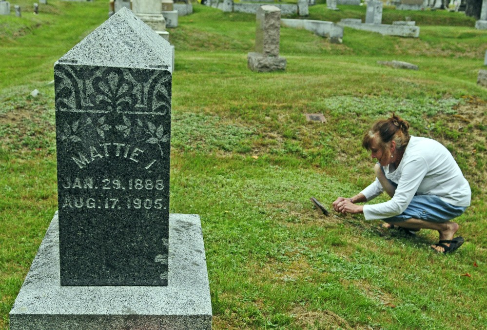 Ellen Bowman of Readfield, who recently wrote a tribute to Mattie Hackett, a 17-year-old girl killed in 1905, looks at another Hackett family grave marker Thursday at Readfield Corner Cemetery.