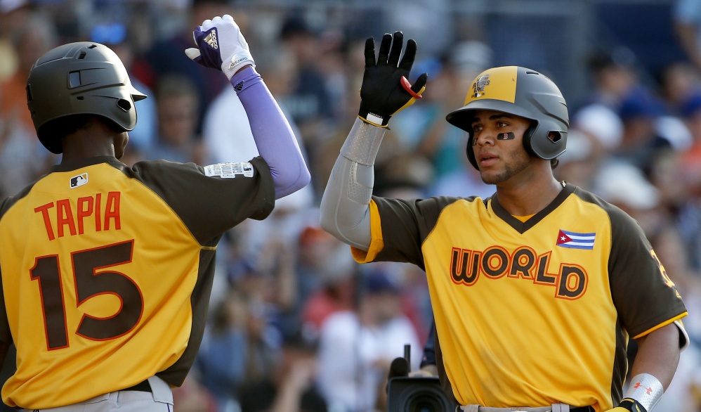 Yoan Moncada of the Boston Red Sox, right, gets congratulations from World teammate Raimel Tapia of the Colorado Rockies, after hitting a two-run homer run against the U.S. team in the eighth inning of the All-Star Futures Game in San Diego. The blast helped the World team win 11-3.