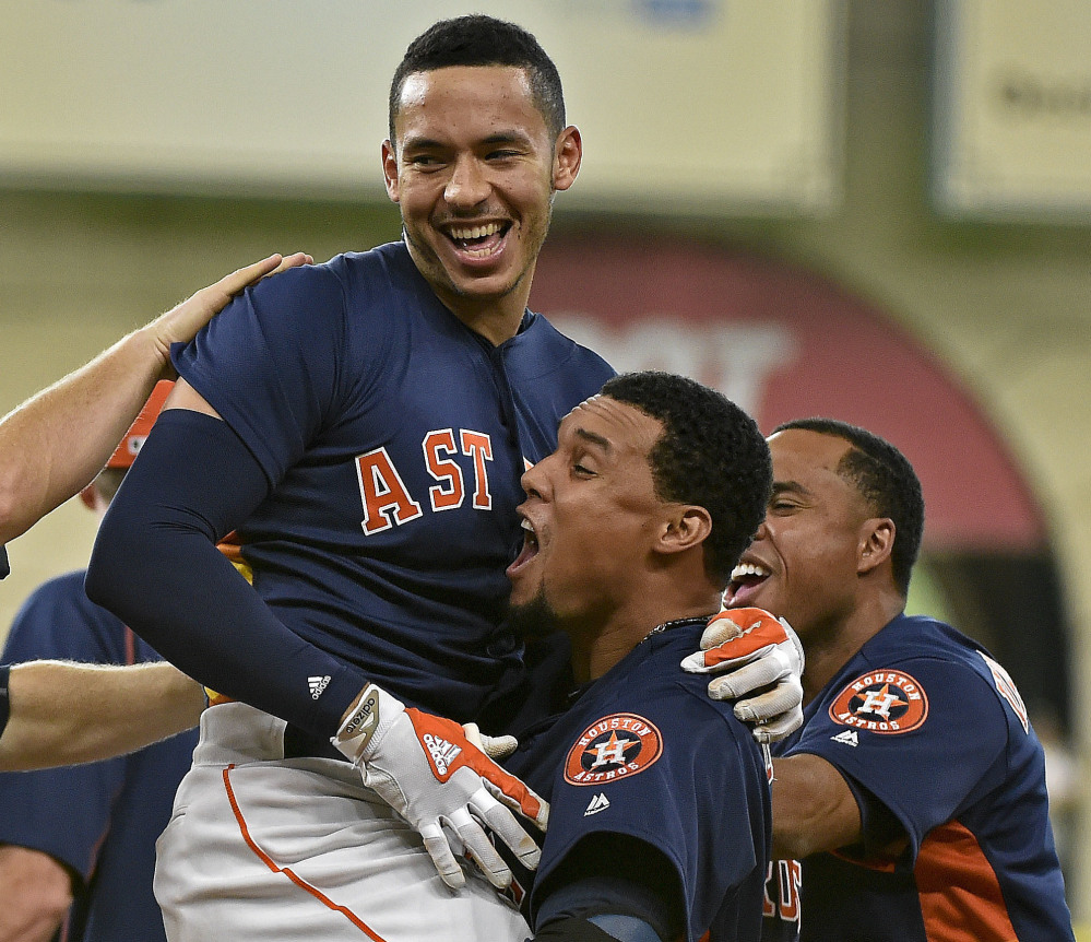 Astros shortstop Carlos Correa, top, celebrates his winning single with teammates on Sunday. Houston defeated Oakland 2-1 in 10 innings.