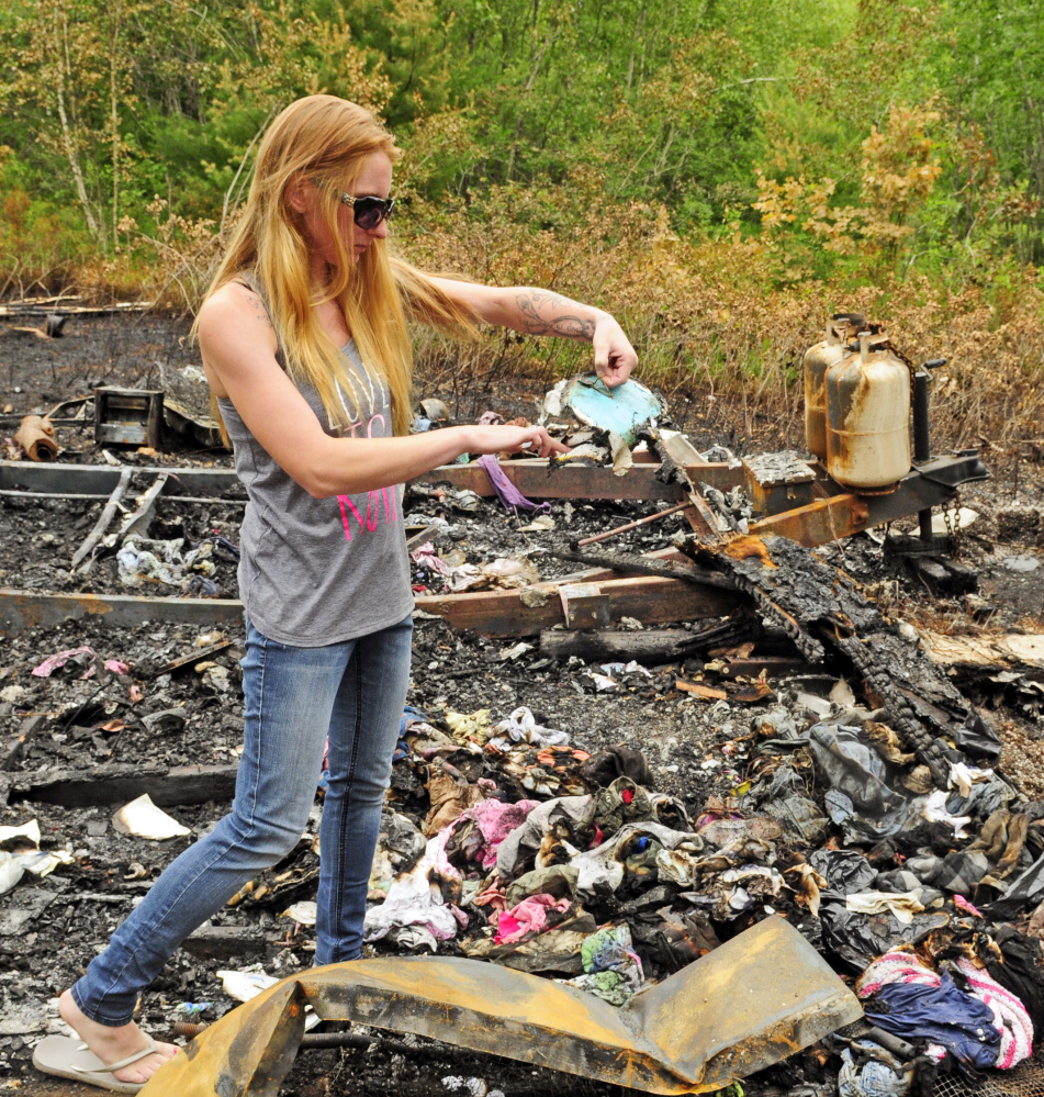 Kristie Baker checks on items that survived the blaze on Thursday at the fire scene in Gardiner. Police arrested Joseph Manganella, 35, of Gardiner on Friday on a charge of arson related to the case.