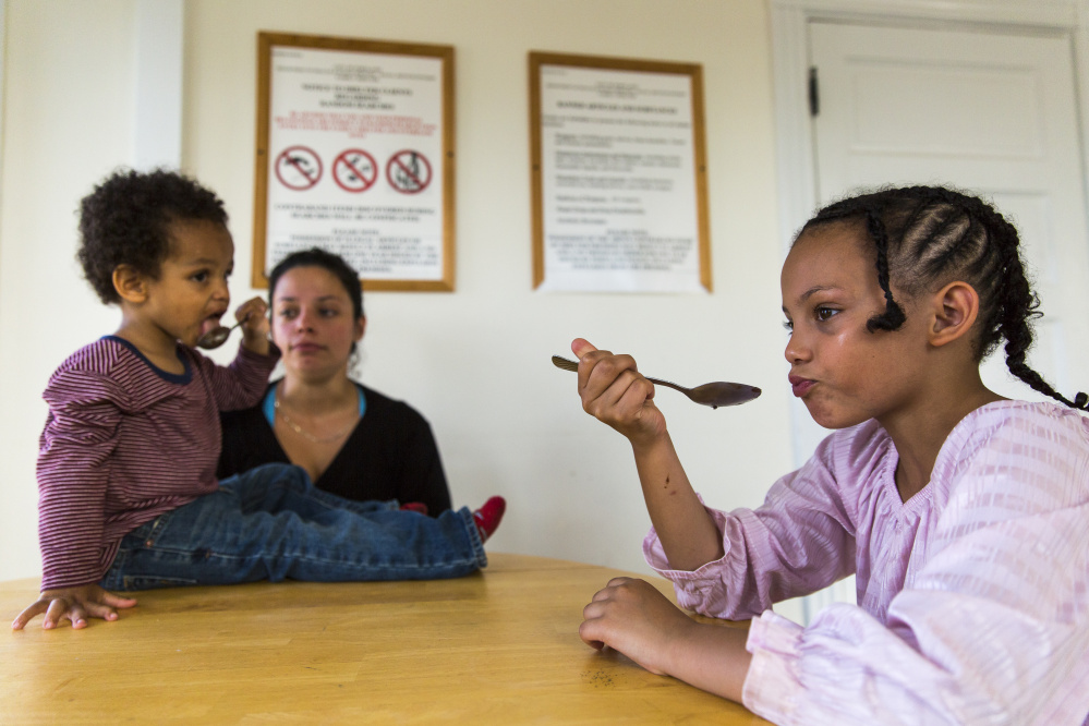 Dizier Pachot and brother Kaden Ware eat peanut butter from spoons alongside their mother, Carmen Ware, a New York native who has had trouble finding a Portland apartment.