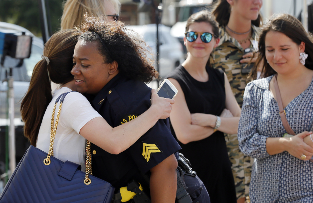 A well-wisher hugs Dallas police Sgt. Jamie Matthews, right, as they visit a makeshift memorial in front of the department's headquarters Monday. Police Chief David Brown said that he is considering requiring everyone on the force to seek counseling in the coming months.