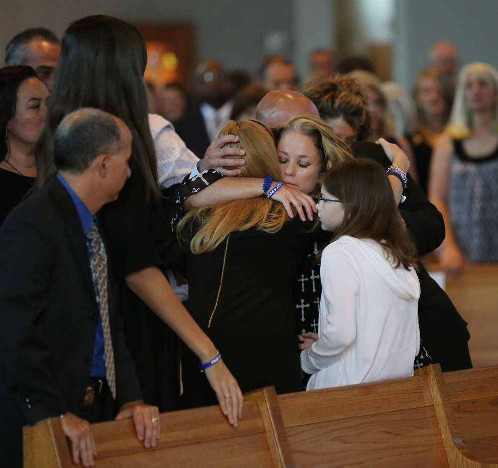 Dallas Sr. Cpl. Marcie St. John, second to right, hugs Heidi Smith, the wife of Dallas police Sgt. Michael Smith, during the funeral for Smith at the Mary Immaculate Catholic Church in Farmers Branch, Texas, on Wednesday. Smith and four other officers were killed during an attack following a peaceful Black Lives Matter protest on July 7.