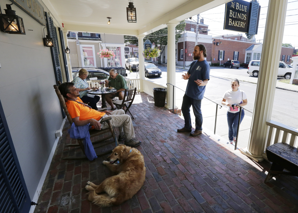 Lev Bryant, manager of the Blue Blinds Bakery, right, engages a customer in a cordial conversation regarding faith on the front porch of the bakery, Wednesday, in Plymouth, Mass. The bakery is owned by a Christian sect, The Twelve Tribes.