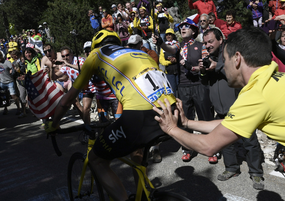 Britain's Chris Froome, is helped after he crashed during the twelfth stage of the Tour de France. His bike ruined, Froome had to temporarily switch to a yellow race assistance bike.