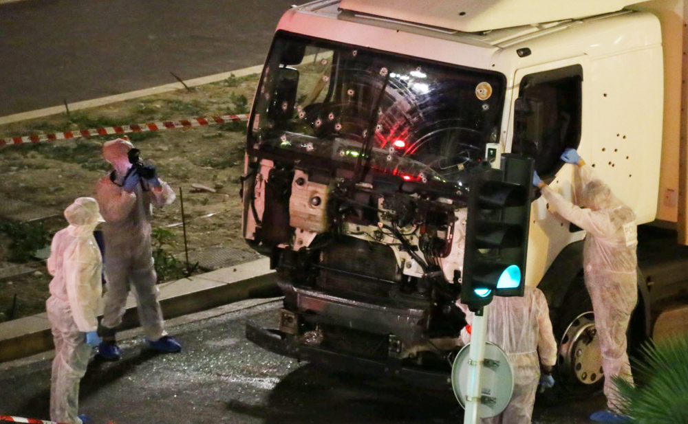 Authorities investigate a truck after it plowed through Bastille Day revelers in the French resort city of Nice, France, on Thursday night, killing at least 84 people.