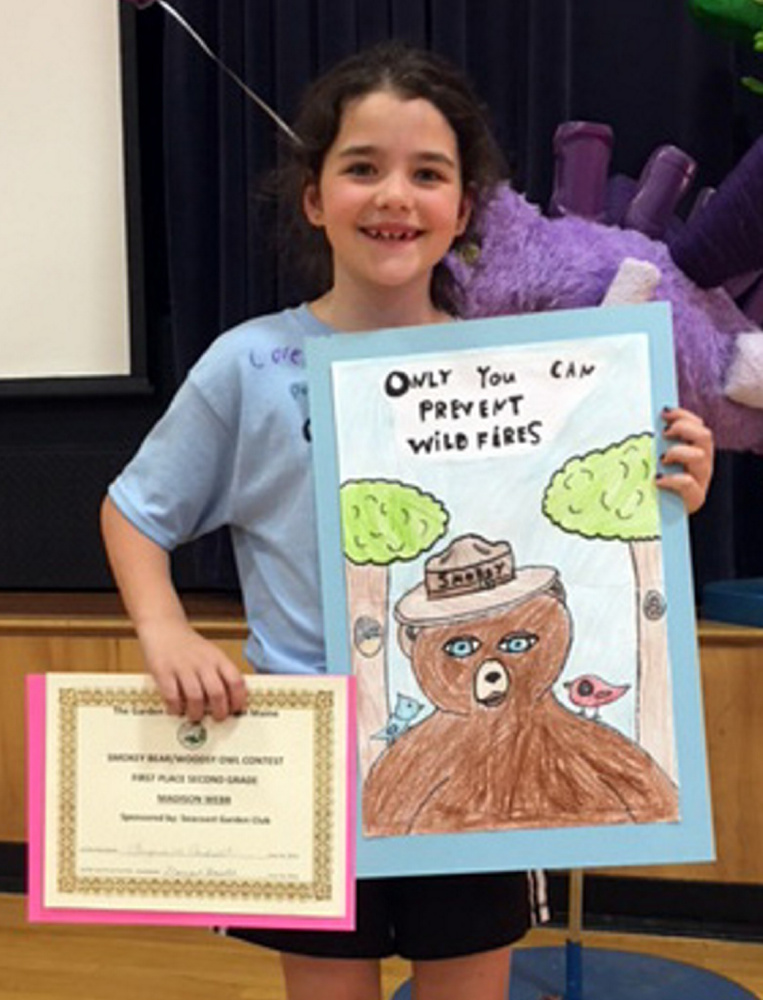 Wells Elementary School student Madison Webb poses with her award-winning poster