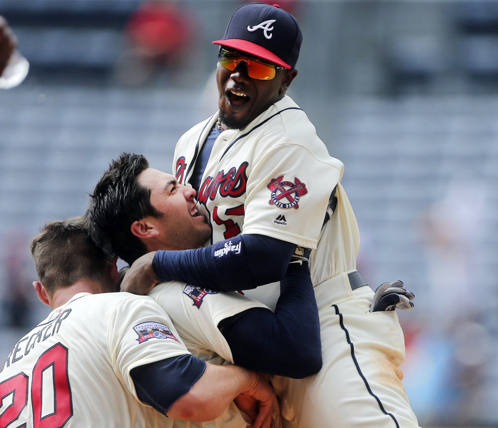 Atlanta Braves' Chase d'Arnaud, center, celebrates with Adonis Garcia, right, and Anthony Recker after driving in the winning run with a base hit in the in the ninth inning of a baseball game against the Colorado Rockies, Sunday, July 17, 2016, in Atlanta. (Associated Press/John Bazemore)