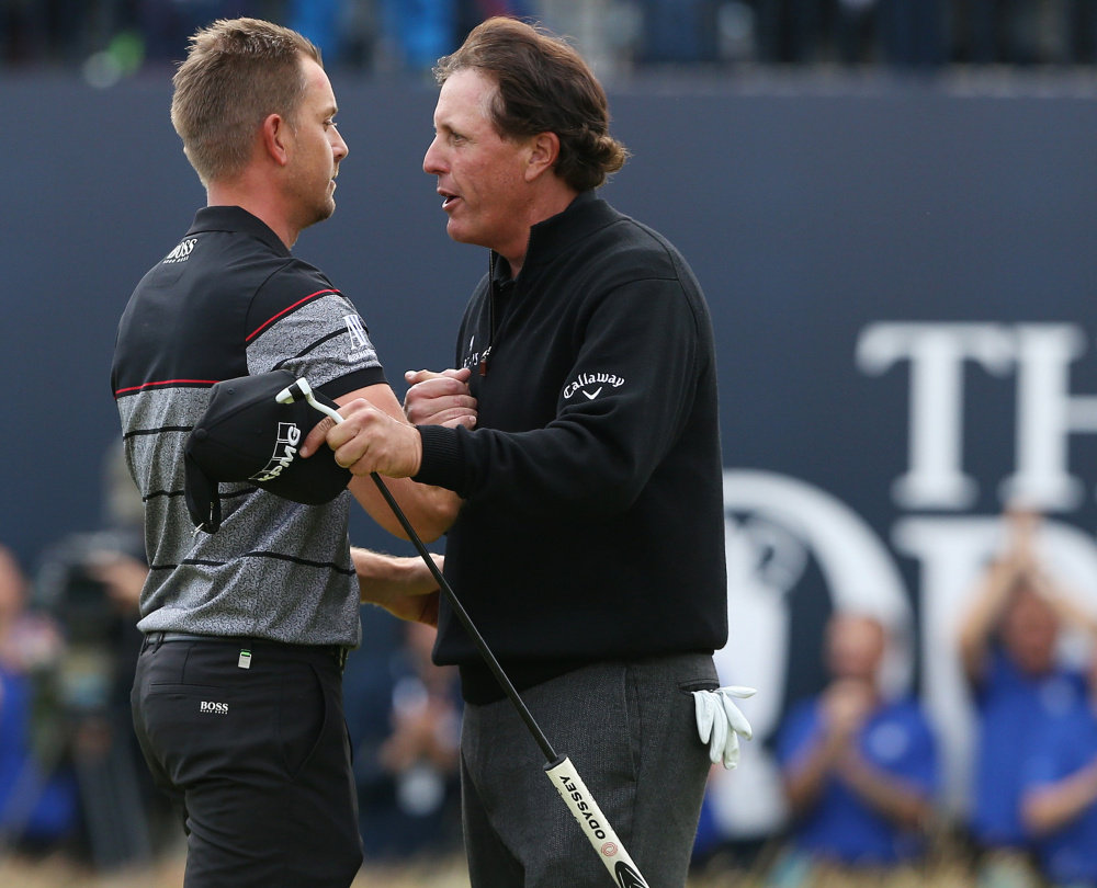 Henrik Stenson, left, is congratulated by Phil Mickelson after winning the British Open on Sunday at Troon, Scotland. Stenson closed with a 63 to hold off Mickelson, who shot a 65.