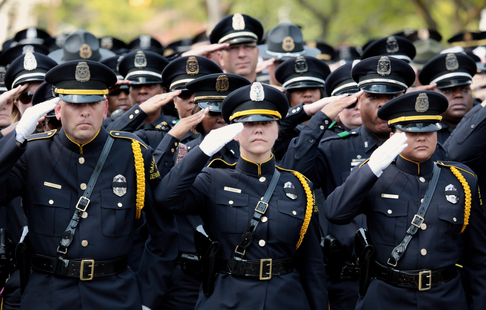 Dallas police officers salute fallen fellow officer Michael Krol on Tuesday.