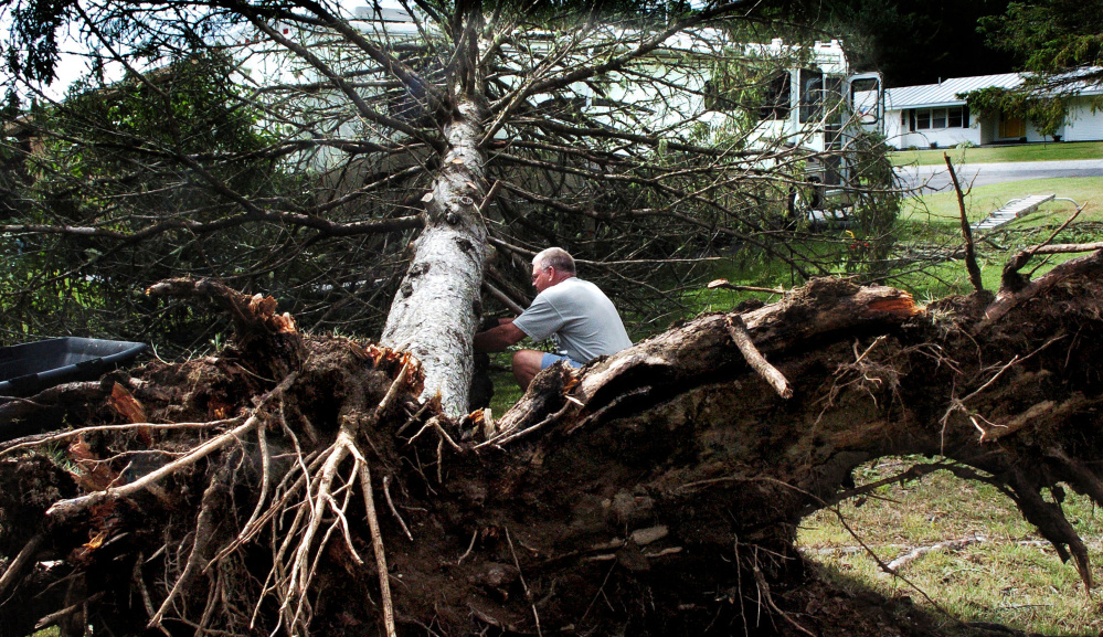 Rick Nadeau positions a floor jack under a tree Tuesday to take weight off his damaged recreational vehicle at his Skowhegan home. In some areas, road blockages are making it hard to get CMP crews to downed wires.