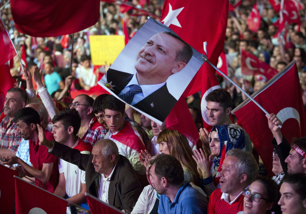 Government supporters wave Turkish flags and hold a picture of Turkish President Recep Tayyip Erdogan during a rally in Taksim Square in Istanbul on Tuesday. The Turkish government accelerated its crackdown on alleged plotters of the failed coup against Erdogan and he called the attempted putsch