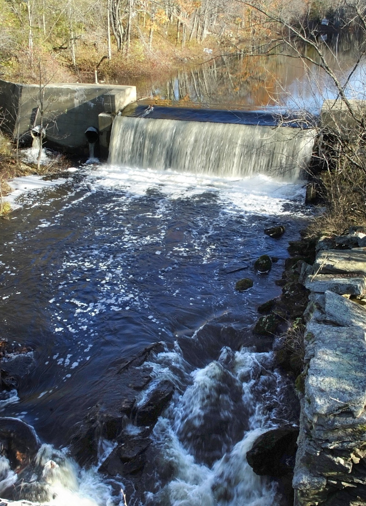 The Sheepscot River flows over the Coopers Mills Dam in Whitefield in 2007. Local officials learned Tuesday that federal money will be available to help pay for the dam's removal.